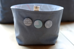 Grey canvas fabric basket with badges with patterned lining